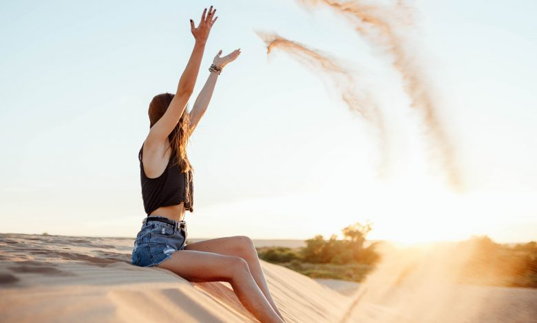 Момиче, което си подхвърля пясък на плажа